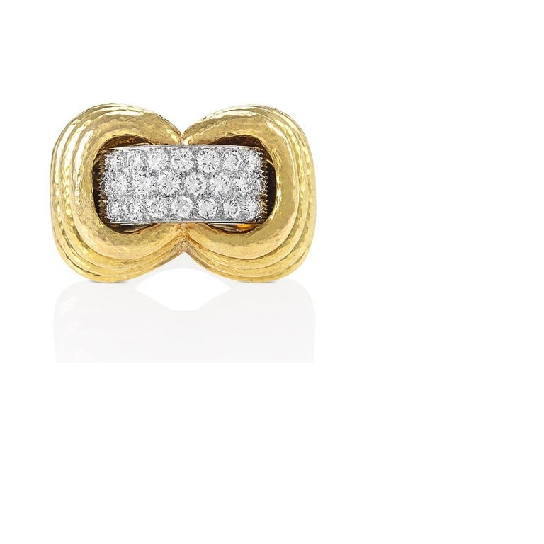An 18 karat gold, platinum and diamond ring, by David Webb. The hammered bombé form mount with stepped sides centers a band of 21 round brilliant-cut diamonds, approximate total weight 2.15 carats, with a F/G color and VS clarity.    This chunky,