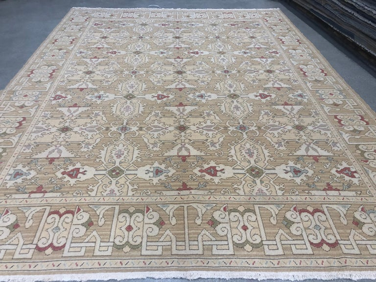 A traditional design receives a contemporary treatment in this deftly executed intricate patterned rug. Red, blue, green, yellow, beige and taupe against a tan background. Handmade in Europe. Wool.