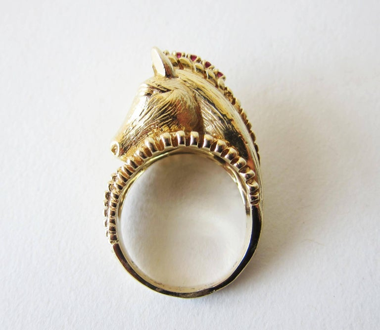 1970's 14k gold, ruby and diamond horse head ring, creator unknown.  One diamond in the forehead and 6 small rubies in the mane of the horse makes up this statement ring.  It is a finger size 8.5 and sits about 1/2