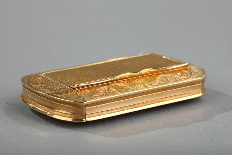 Rectangular box with rounded corners. The hinged lid as well as the bottom are embellished with an intricate geometric pattern framed with rinceaux motifs on a matte gold background. A button serves to open the box.  Weight: 1.8 oz (52