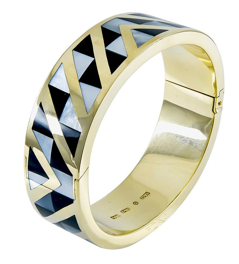 A very compelling piece of jewelry:  a hinged bangle bracelet.  Made and signed by TIFFANY & CO.  Set with black jade and mother-of-pearl in a striking geometric pattern. The pattern is seamless, and continues around the bracelet, front and back.