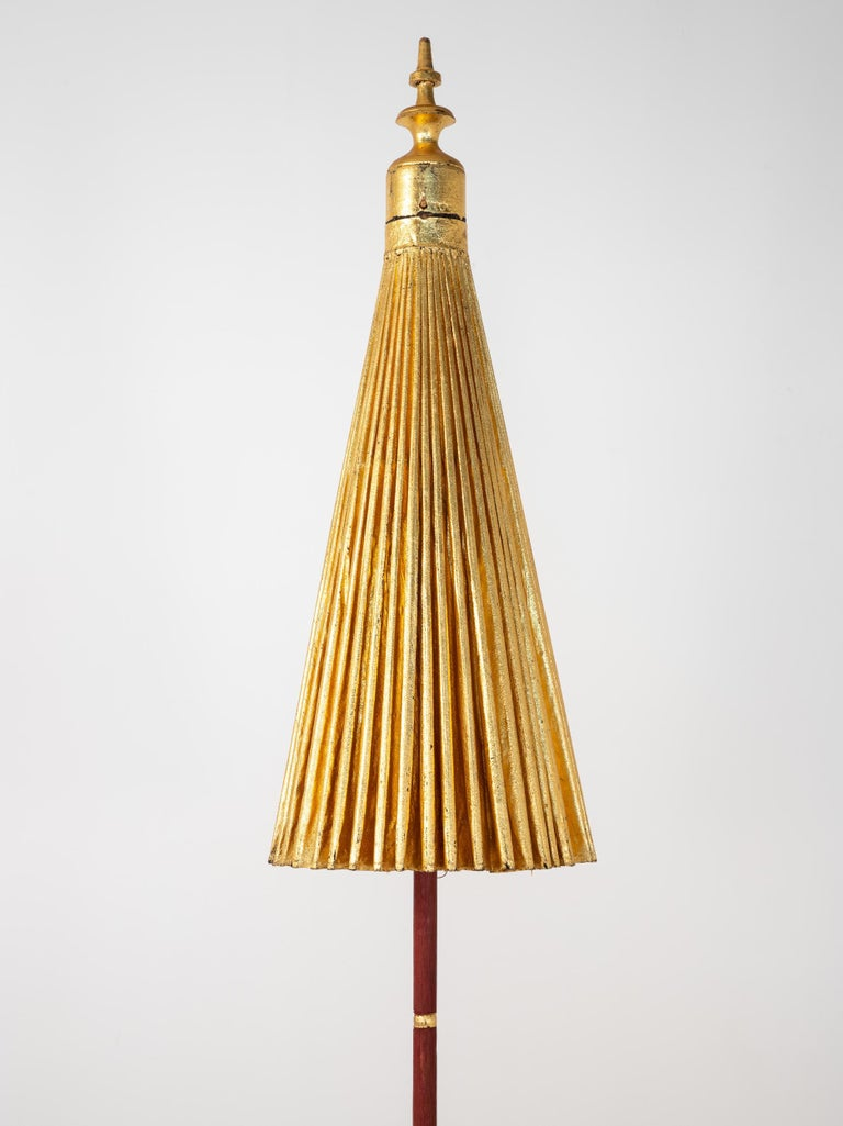 Stunning sun umbrella with a gilt exterior and a painted wood column with a gold finial at the top. The gold umbrella opens to reveal a brilliant pattern of color created by woven threads anchored by a black interior. The column of the umbrella is