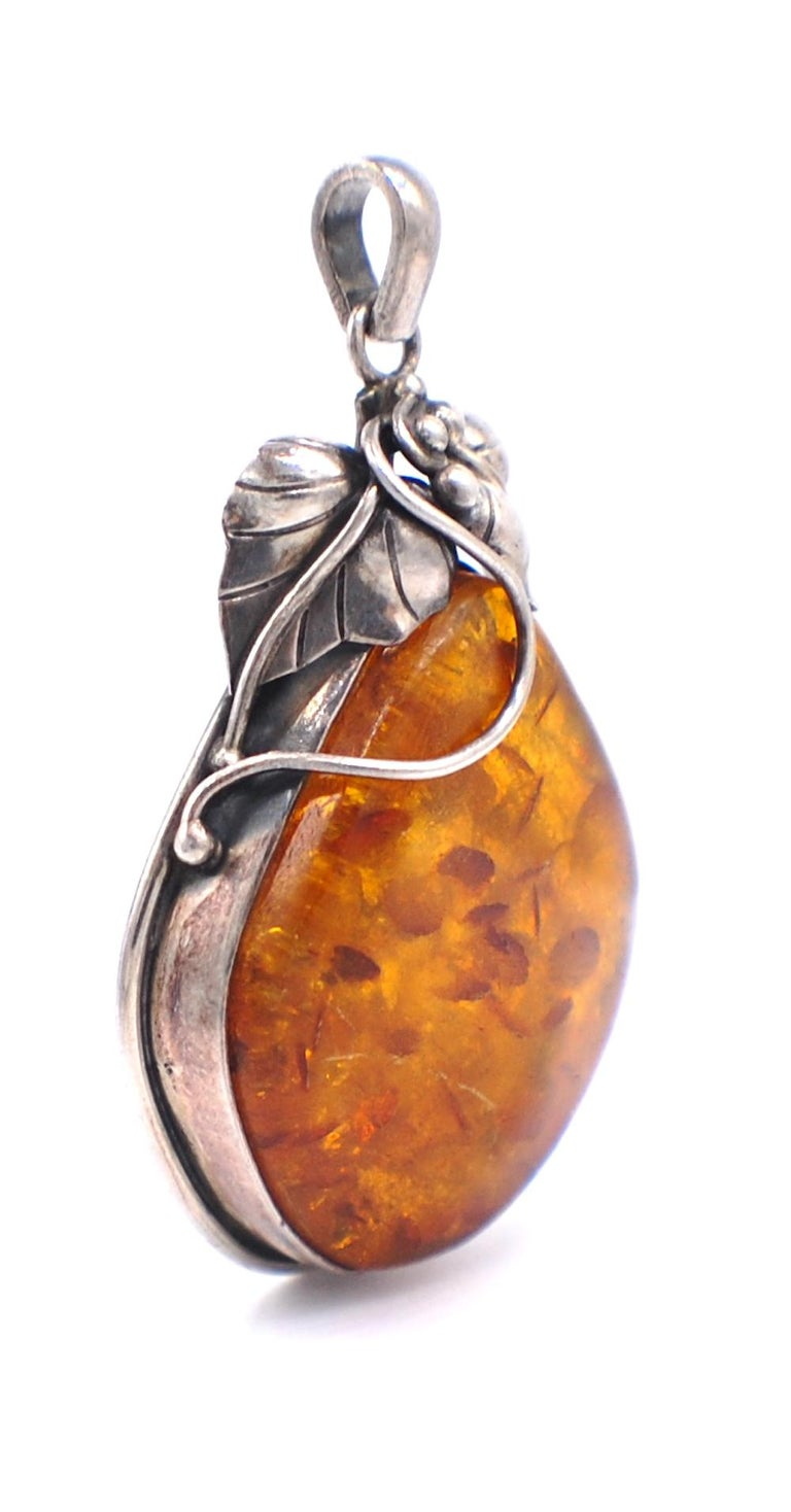 Flicks of Colored Amber incased in a bezel setting with leaf designed accent to artistically decorate this pendant. The pendant measures 2-1/3 inch length with another 1/2 inch long chain bail. The width of pendant is 1-1/2 inches. Colored amber are
