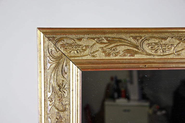 Delicate golden Art Nouveau mirror built in Austria circa 1900 in the glorious times of the famous Art Nouveau period. This mirror shows a beautiful composition gold covered frame adorned by lovely flower ranks, an epitome of the Art Nouveau era.