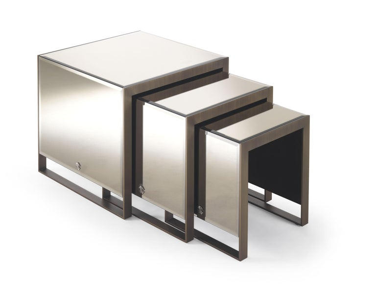 Square side tabletop covered with leather bevelled bronze mirror. Metal structure in brushed bronze finishing.