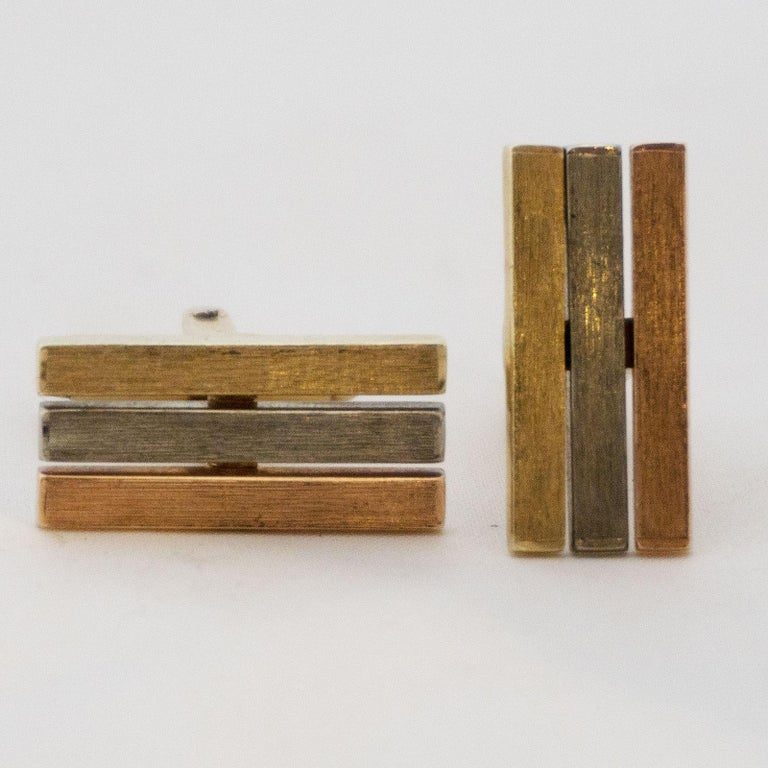 Golden cufflinks Tricolor  These gold cufflinks are worked in three colours on the upper side. This was achieved by a layer in yellow gold, red gold and platinum. The body and the bridge mechanism are made of yellow gold 585.  For the big gala even