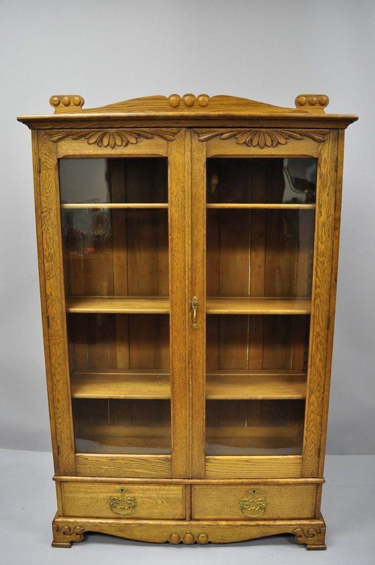 Antique golden oak Victorian two-door China cabinet bookcase with two dovetail drawers. Item features solid wood construction, beautiful oakwood grain, nicely carved details, two glass swing doors, working lock and key, plate groves, two dovetailed