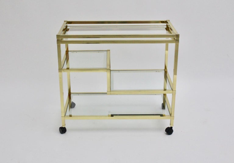 This Bar cart in the style of Romeo Rega consists of a gilded frame construction with four glass plates in various sizes. The glass plates are surrounded with a silver edging. Also the bar cart shows 4 wheels for a good mobility. The vintage