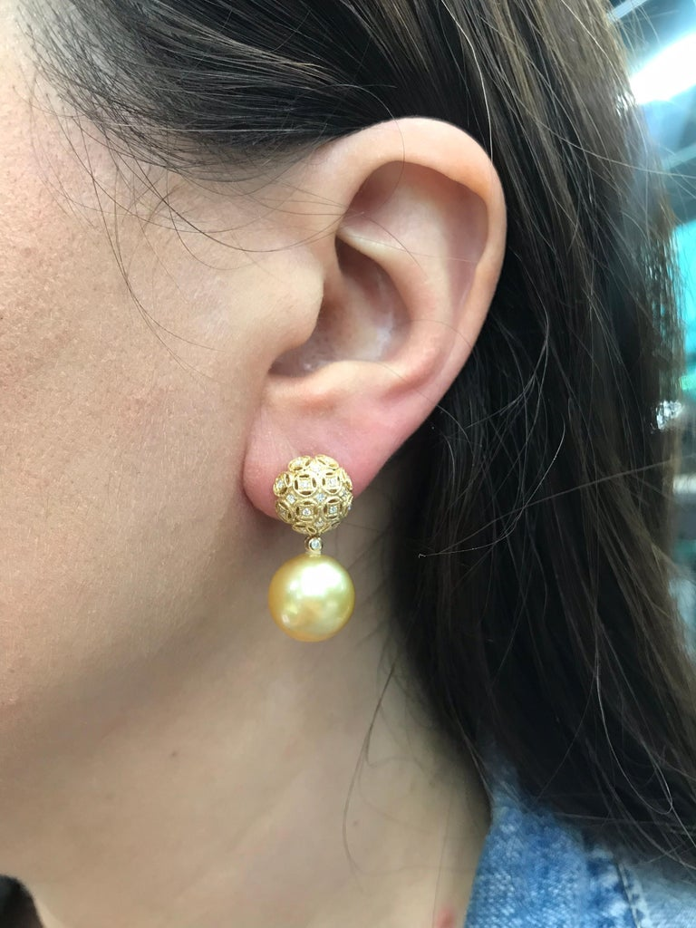 18K Yellow gold drop earrings featuring two Gold South Sea pearls measuring 13-14 mm flanked with round brilliants weighing 0.30 carats.
