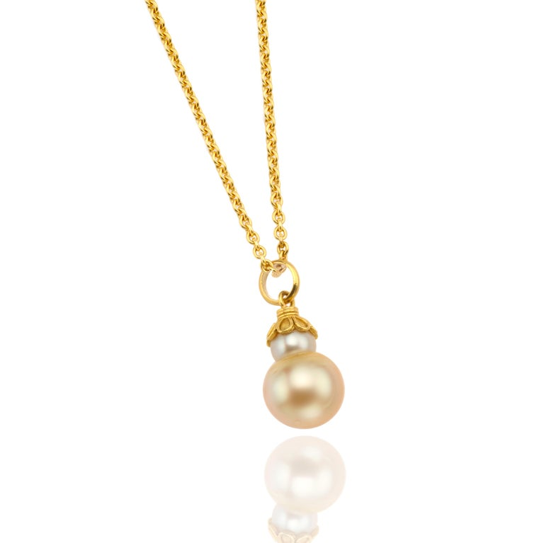 Very lovely double Golden South Sea pearl mounted in 22 karat gold cap. Being the most rare and sought after, South Sea pearls are known for their incredible size and beautiful satin lustre. The pearl measures 13mm in diameter. Shown on small 22
