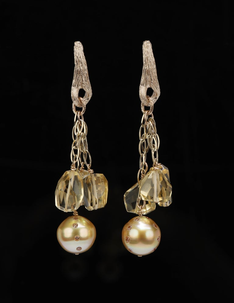 Four gold chains swing under gold vanilla beans.  One chain swings a golden south sea pearl (12mm), embellished by 12, round Champagne diamonds (approximately .64 cts. in weight).  The remaining 3 chains swing faceted, organic shapes of citrine.