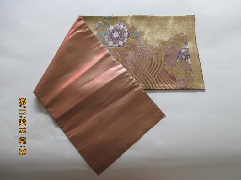 Golden textured woven obi textile depicting flowers in bloom, in shades of deep purple, gold, lavender, green, white, pink and aqua. The pattern fragment is 12