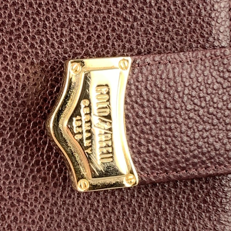 GOLDPFIEL 150th Anniversary book organizer cover comes in burgundy textured leather with a snap closure detailed with a gold tone embossed tip.   Very Good Pre-Owned Condition.  6.25 x 8.75 in.
