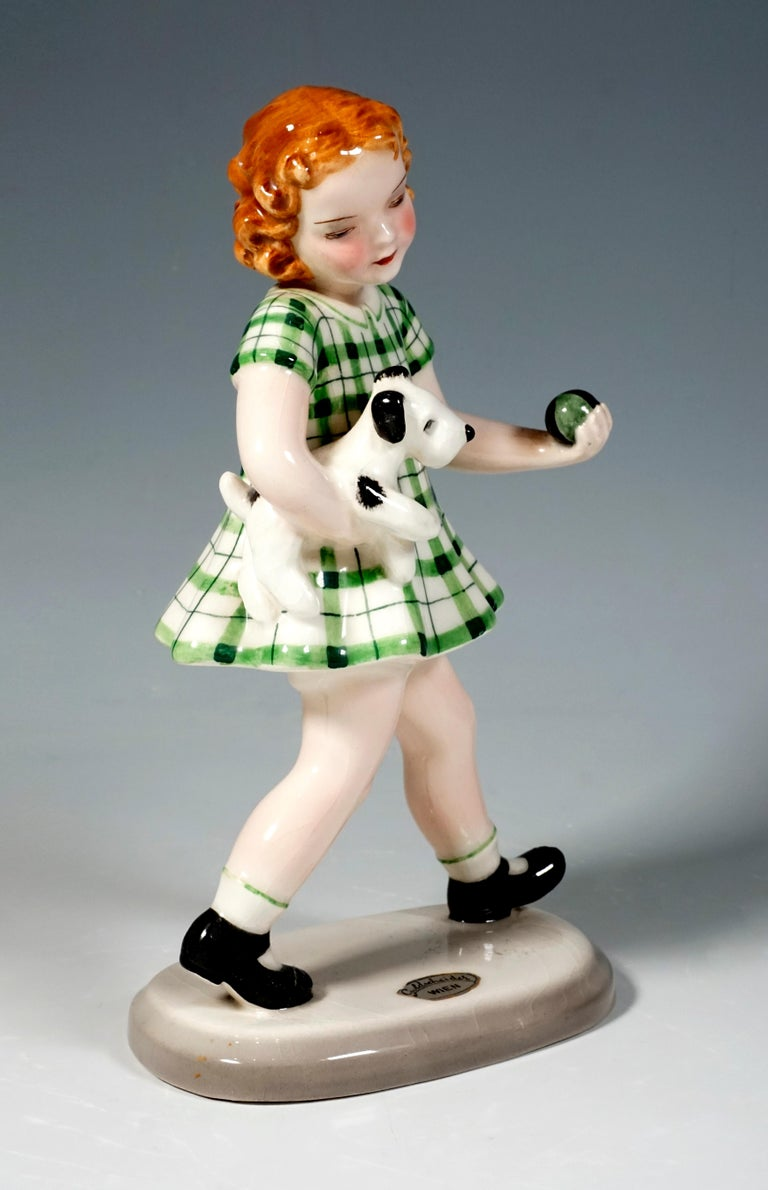 The striding red-haired girl in a green checkered dress carries a small dog under her right arm, in her left hand she holds a small green-black ball. On a beige, oval base.  Designed byAdolf Prischl (1912 - 1970), Sculptor, numerous of his
