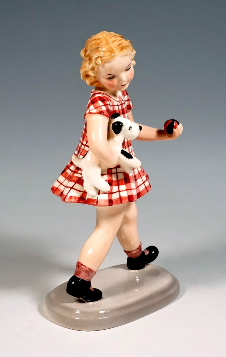 The striding blonde-haired girl in a red checkered dress carries a small dog under her right arm, in her left hand she holds a small red-black ball. On a beige, oval base.  Designed byAdolf Prischl (1912 - 1970), Sculptor, numerous of his models