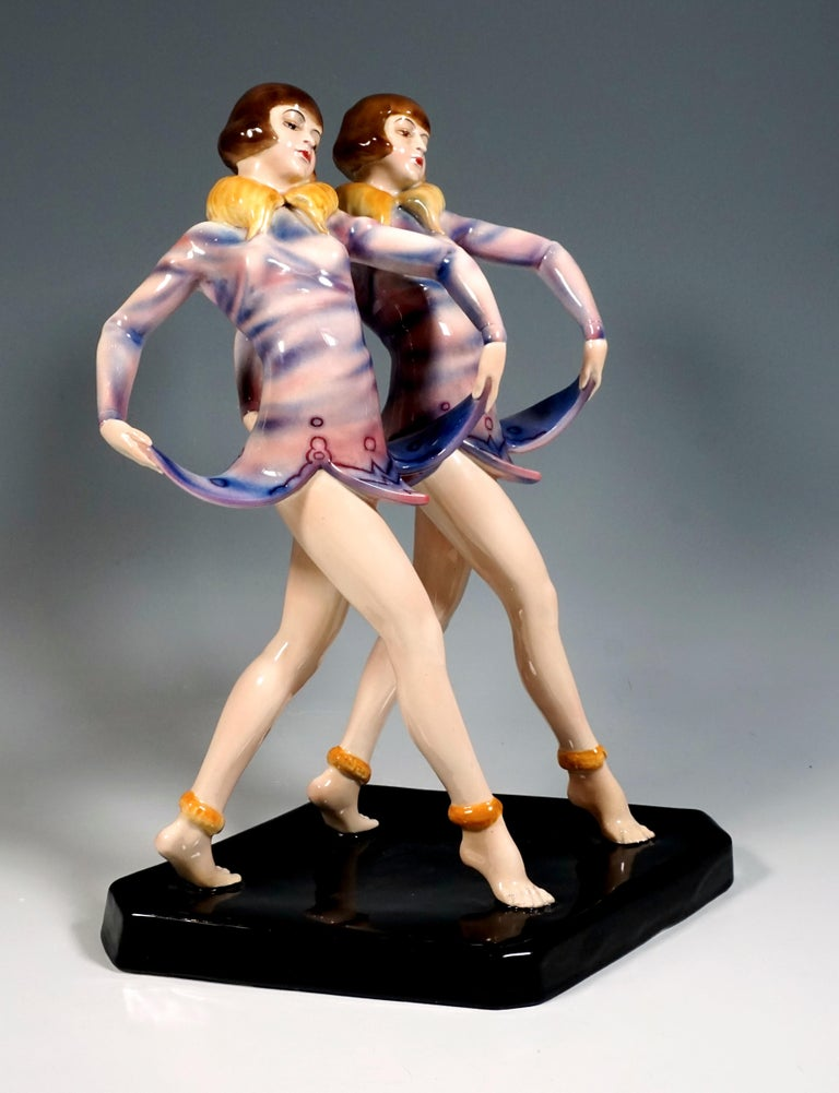 Most Remarkable Rarest Goldscheider Art Deco Figurine Group of the 1930s: Two standing young revue twin dancers with pageboy hairstyle, taking a step forward. At the same time, they lift the bellflower-shaped hem of their short purple dress with a
