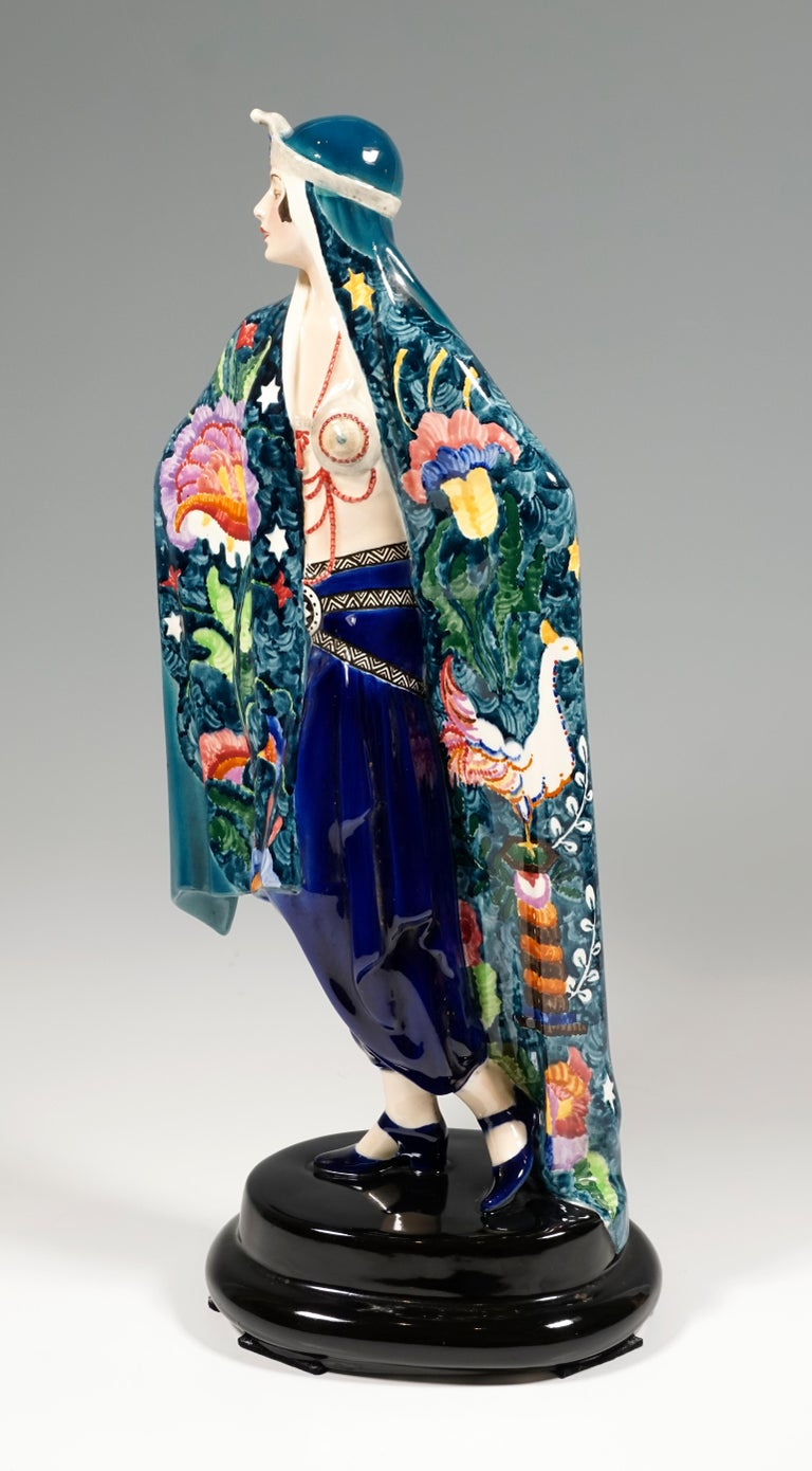 Very exceptional decorated Goldscheider Art Deco ceramic figure of the 1920's: Depiction of a standing, proudly looking to the side lady in oriental garb. She is wrapped in a large blue-green cloth that reaches down to the floor, the front of which