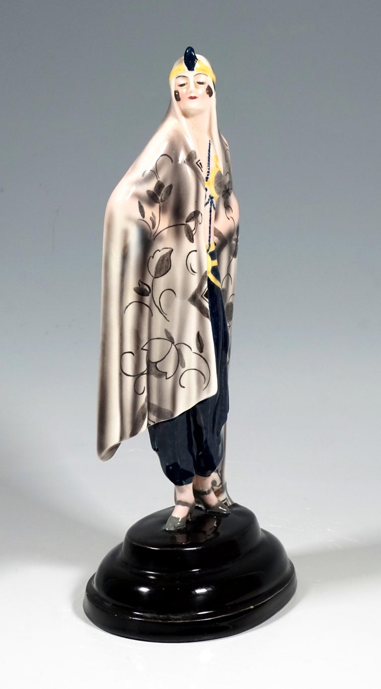 Depiction of a standing lady, proudly looking to the side in oriental garb. She is wrapped in a large beige cloth that extends to the floor, the front is decorated with a stylized, gray-shaded flower and tendril pattern and covers her hair, held in