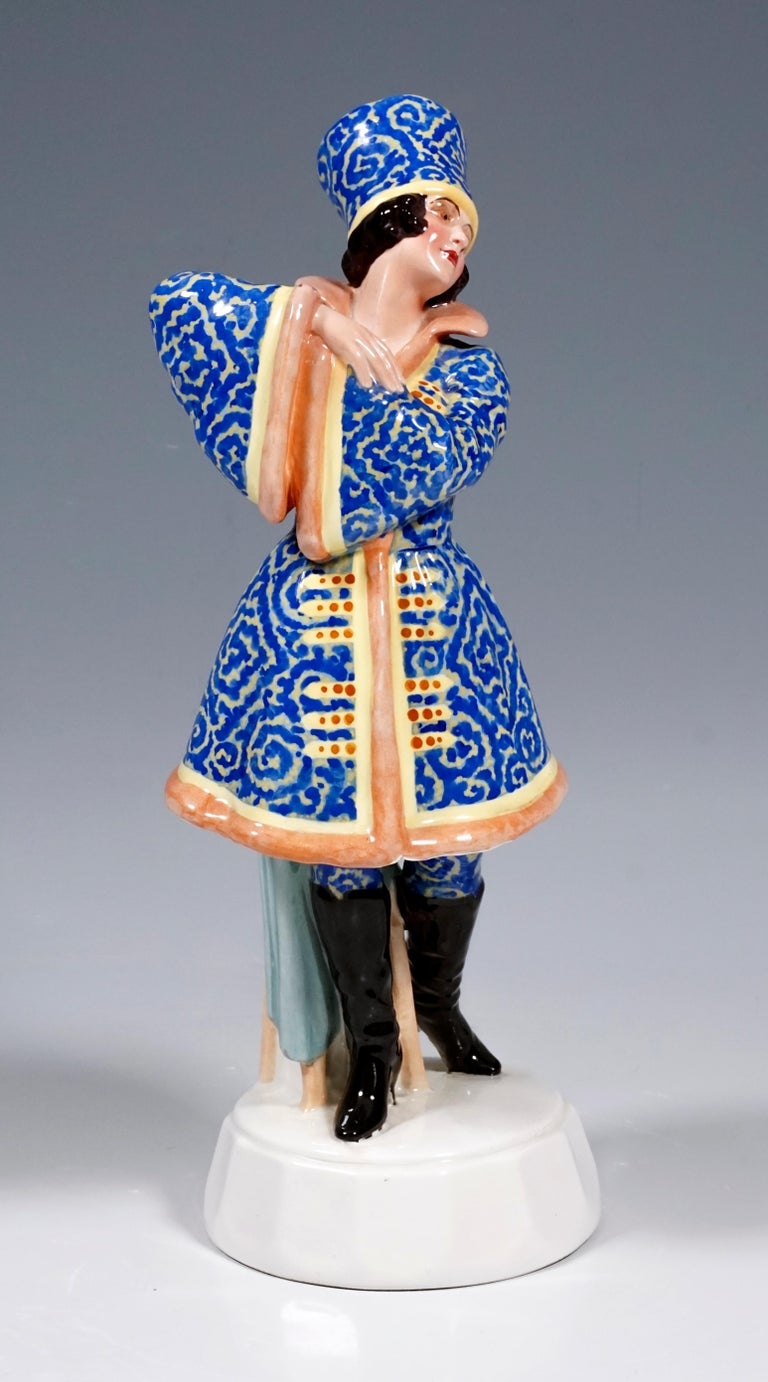 Very rare Goldscheider Vienna Figurine of the 1920s A standing dancer looking to the side with arms crossed and raised in front of her is shown. The young lady wears a Russian costume, decorated with elaborate blue embroidery, with a high fur cap