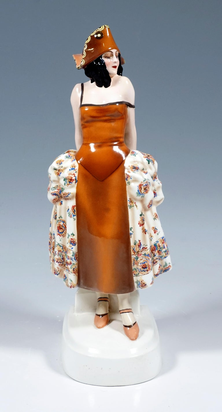 Rare Goldscheider Vienna Figurine of the 1920s: Standing young lady in a brown carnival costume based on a rococo dress with a cream-colored skirt decorated with colored flowers and a brown tricorn, supporting herself with both arms on a column at