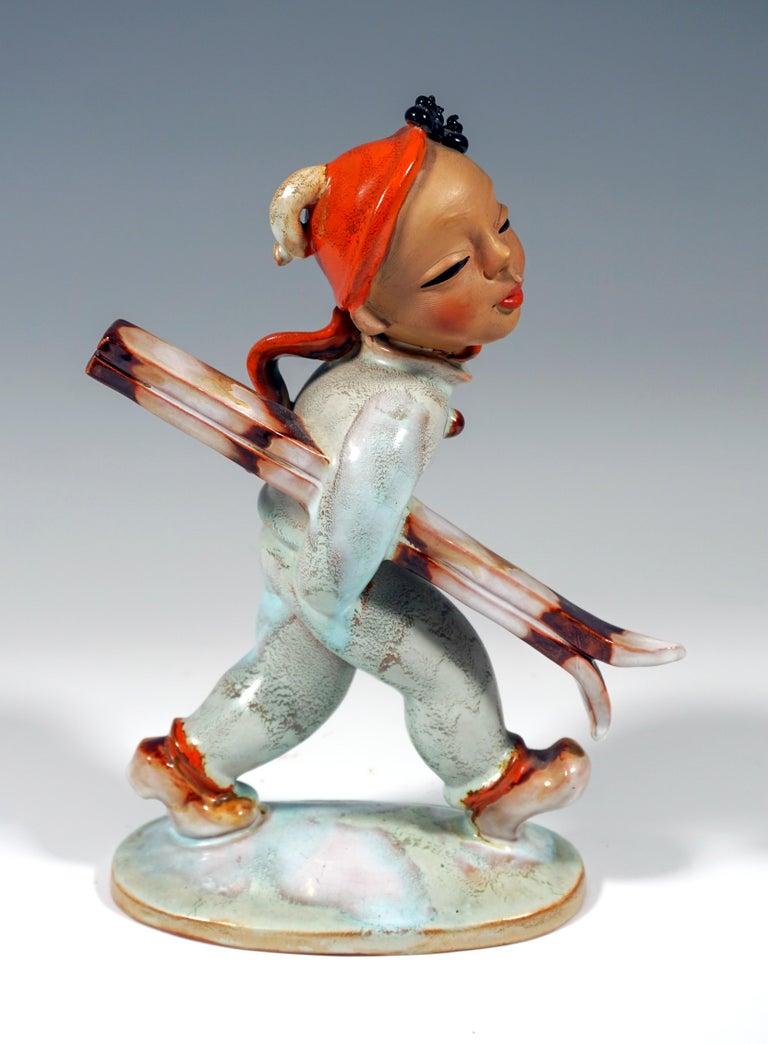 Remarkable Goldscheider Art Déco Figure by Kurt Goebel The young skier in a light blue overall wears a red CAP, from under which his black curls peek out, and a red scarf. Clutching his skis under his right arm, he walks along. On an oval snow