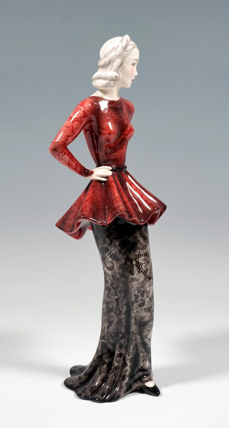 Depiction of Marlene Dietrich as a woman of fashion in a long, narrow lace skirt in black with a red, low-cut, waisted top, her arms on her hips. Her pointed black shoe protrudes from under the robe in front. The figure is based on the skirt hem