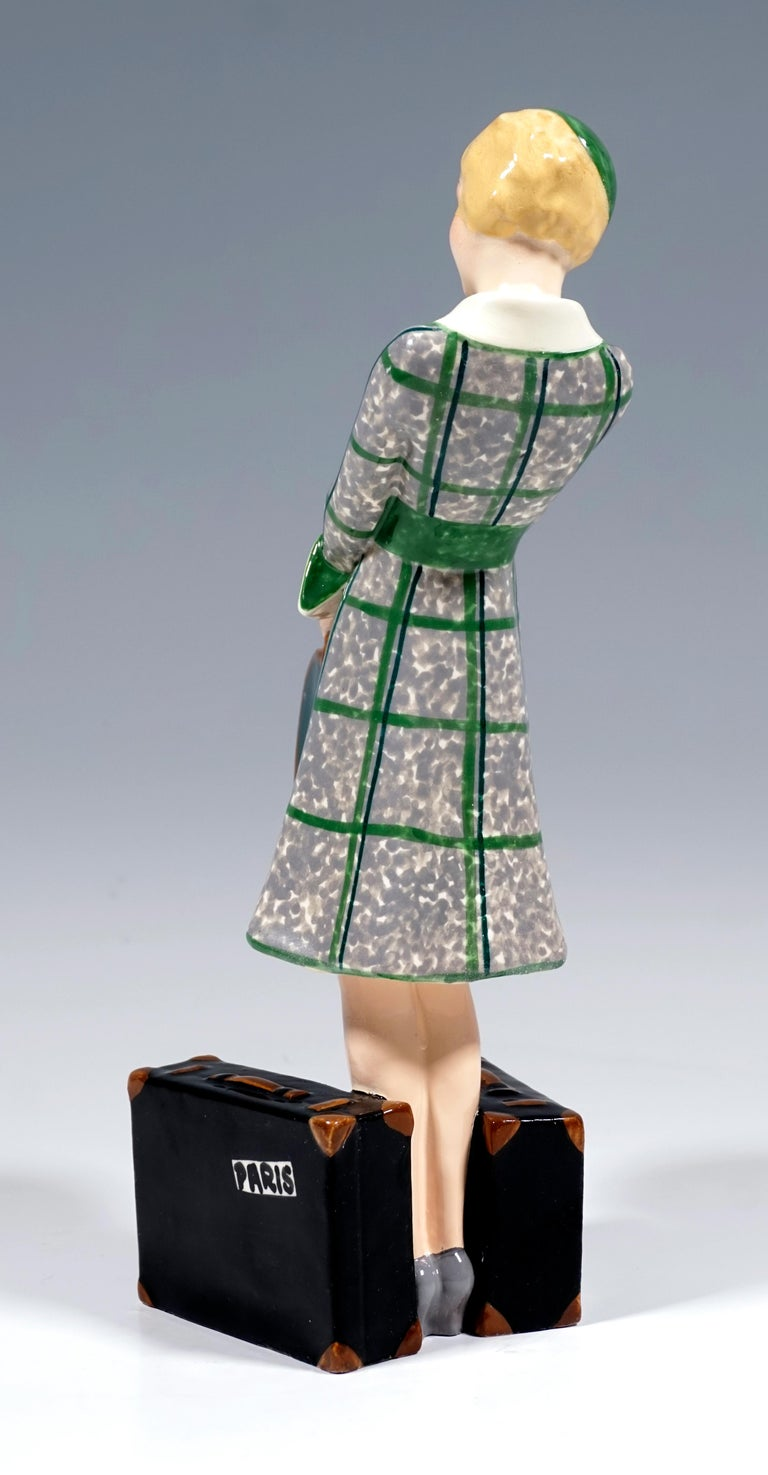 Very rare Goldscheider Vienna ceramic figurine of the 1930s: Depiction of a blond, elegant lady in a gray-green dress and a matching hat standing between two black suitcases, holding a green bandbox in front of her with both hands. The figure is