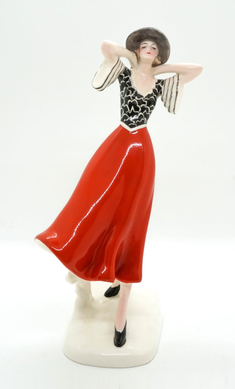 The striding girl leans slightly backwards into the wind and holds her hat on the back of her head with both hands. She wears a dress with a black and white patterned tight-fitting top with wide sleeves, a gust of wind blows the bright red skirt