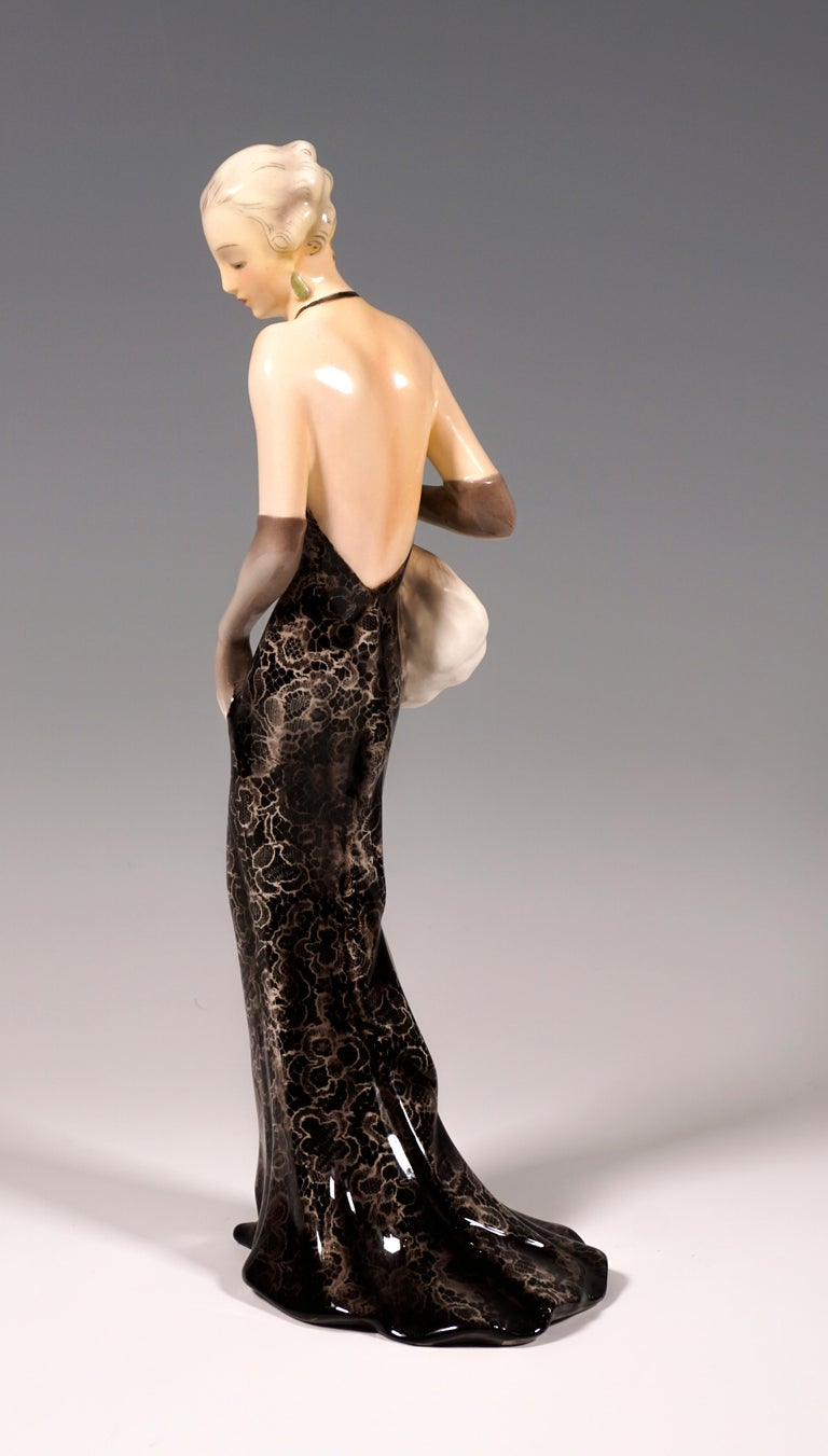 Very rare goldscheider Vienna figurine of the 1930s: Depiction of an elegant lady in a long, tight-fitting, backless dress made of black lace and a wide skirt part. She also wears long gray gloves, her hair pinned up and matched to the color of the