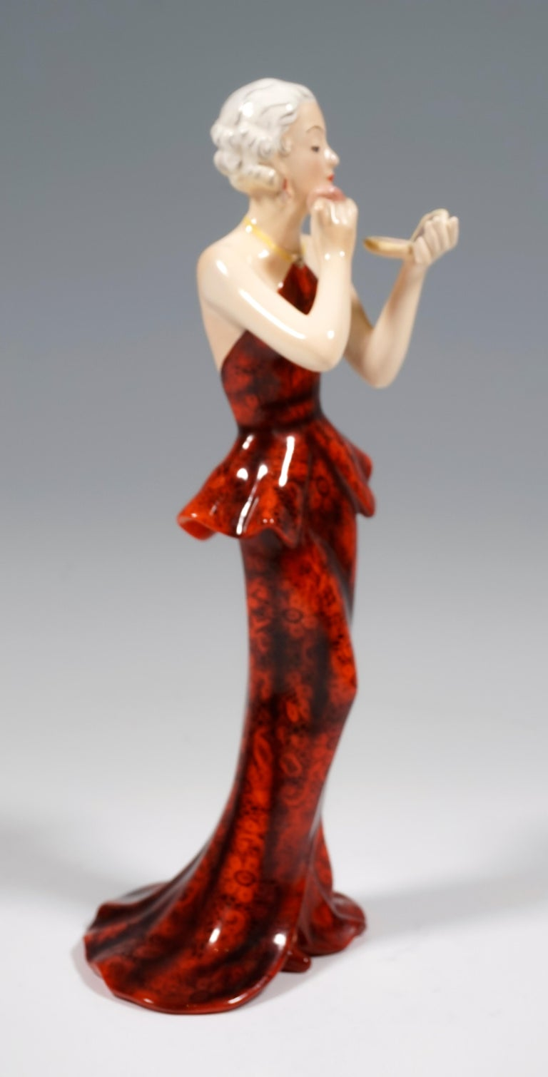 Very rare Goldscheider Vienna figurine of the 1930s: Representation of an elegant lady in a long, tight-fitting, backless dress made of red-black lace with a flared top and part of the skirt swinging out on the floor. She wears her hair pinned up