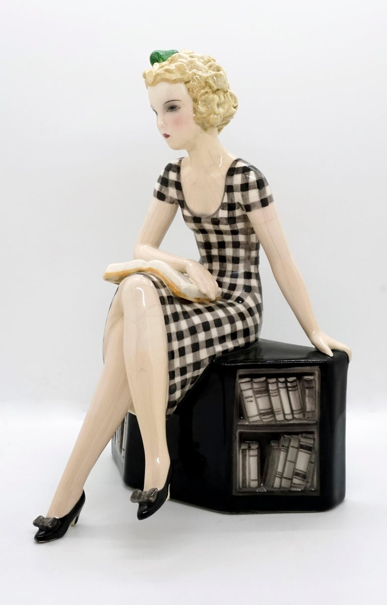Very rare goldscheider Art Deco ceramic figurine. The girl with blond curly hair and a green bow in her hair, wearing a black and white checked dress, is sitting cross-legged on a low black bookshelf. Looking lost in thought, she lays her right