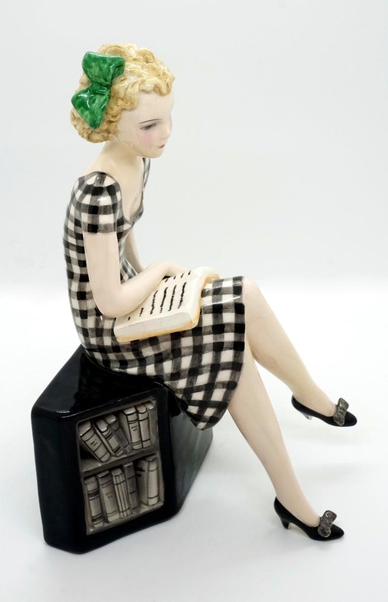 Hand-Painted Goldscheider Vienna Girl with Book Sitting on a Bookshelf by Dakon, circa 1935