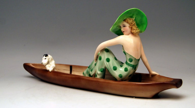 Goldscheider Vienna Lady in Canoe, with Fox Terrier. Model created 1935 by Stefan (= Stephen) Dakon (1904 - 1992). Made circa 1936-37.  model number 7256 / 162 / 16  Hallmarked: painter's sign & two signatures 'Dakon' at reverse side of canoe