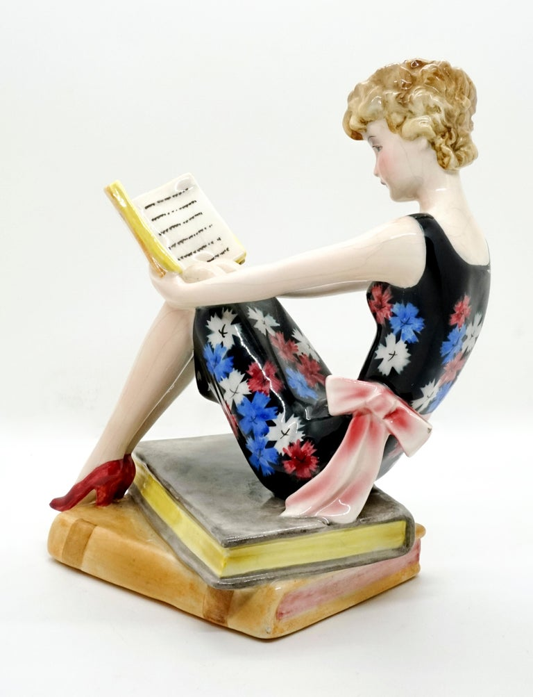Very rare goldscheider Art Deco ceramic figurine. A young lady with blond curly hair, a flowered summer dress and a large bow around her waist, is sitting on a pile of large books that also serves as a pedestal, reading a book, which she is holding