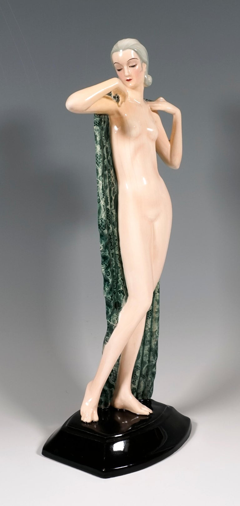 Very rare Goldscheider Ceramic Figurine of the 1930s: The standing pretty young lady with her hair combed back and pinned up at the neck merely covers her nakedness with a large, green and white cloth that she holds behind her and that gently