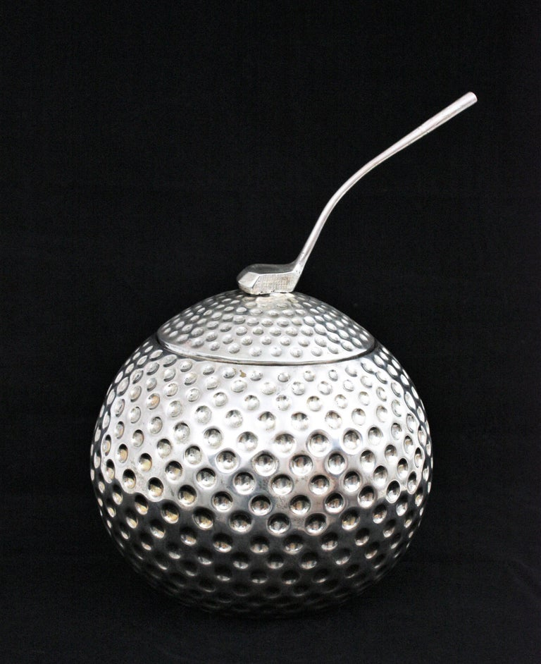 An exquisite Hollywood Regency silvered metal golf ball shaped ice bucket or wine chiller. Designed and manufactured by Valenti. Spain, 1960s. This unusual golf ball was designed to be used as an ice bucket or wine chiller. It has a golf club on