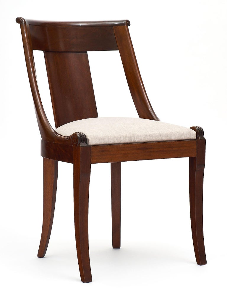 A French antique empire style set of eight mahogany gondola chairs. This set is very comfortable and sturdy with the Classic curved backs and front saber legs. The seats have been newly upholstered in dove gray linen blend.