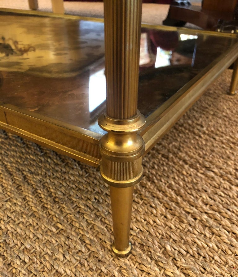 Of solid gilt-bronze in the timeless neoclassical style favored by Louis XVI of France and revitalized by Maison Jansen in the 20th century; the inset oxidized mirrored top with reeded apron and raised on reeded supports joining a similar lower