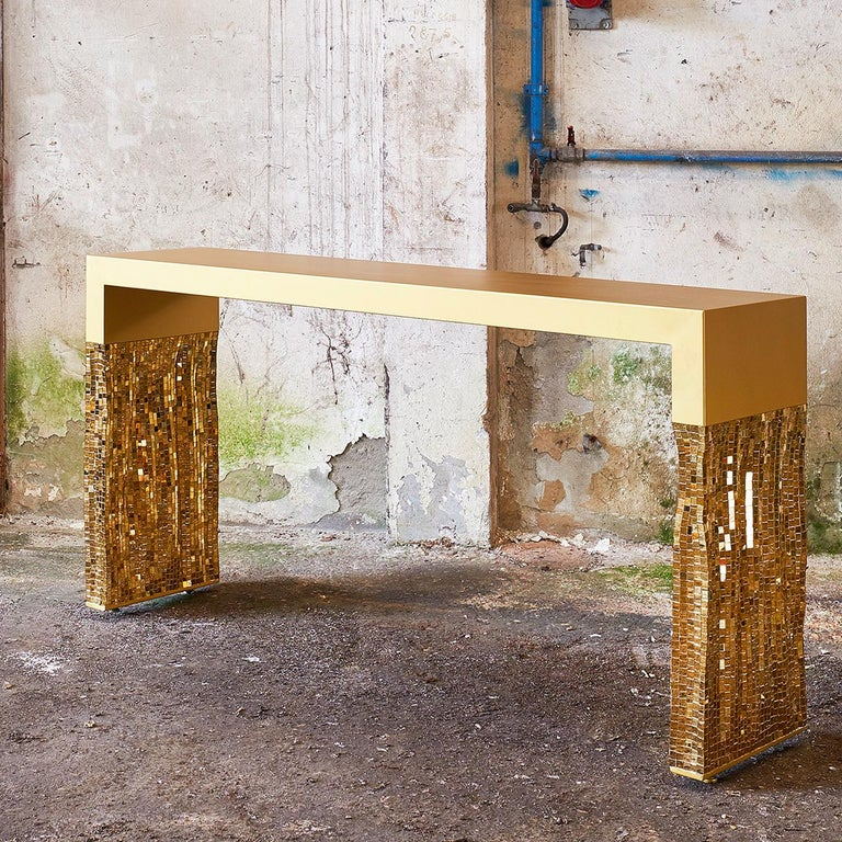 Merging industrial and Classic materials into a minimalist silhouette, this console is the ultimate statement in style and sophistication. The sleek stainless steel frame has a gold satin finish and features a rectangular silhouette with bold legs