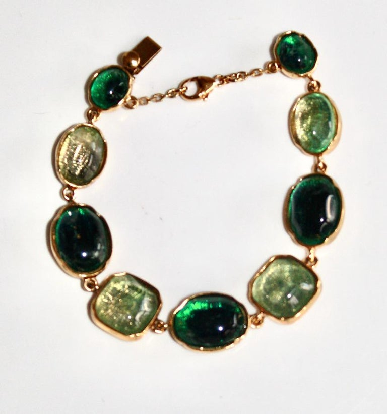 Hand tinted rock crystal in shades of green set on 24Kt gilded bronze. Carved mounting. Signature on the back. Security chain.