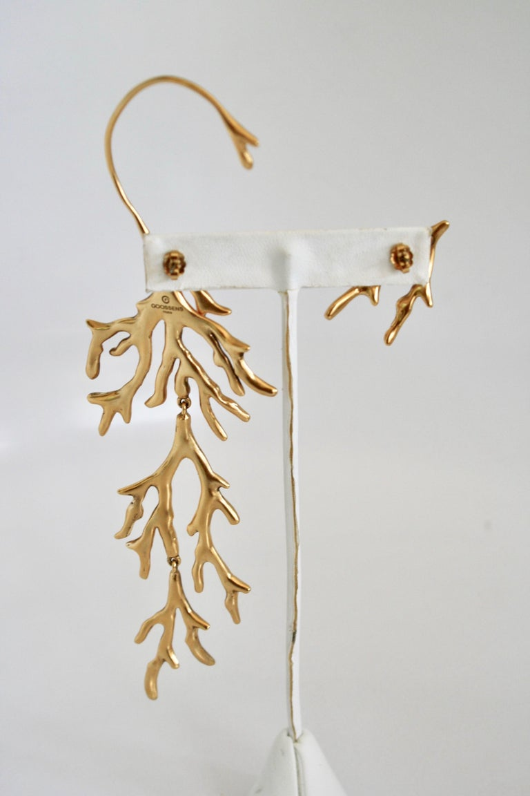 The House of Goossens revisits the iconic themes of its founder, Robert Goossens: coral, shell, leaves and water lilies. These asymmetrical metal earrings are tempered in a bath of 24 carat gold and adorned with a branch of coral, a call-back to