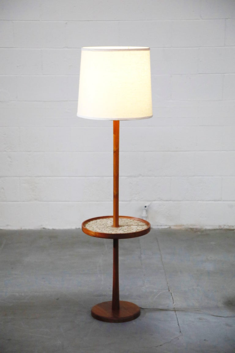 This classy floor lamp with built-in side table by Gordon and Jane Martz for Marshall Studios is in incredible original vintage condition with a beautiful light patina. The built-in round side table is covered in round white and light colored