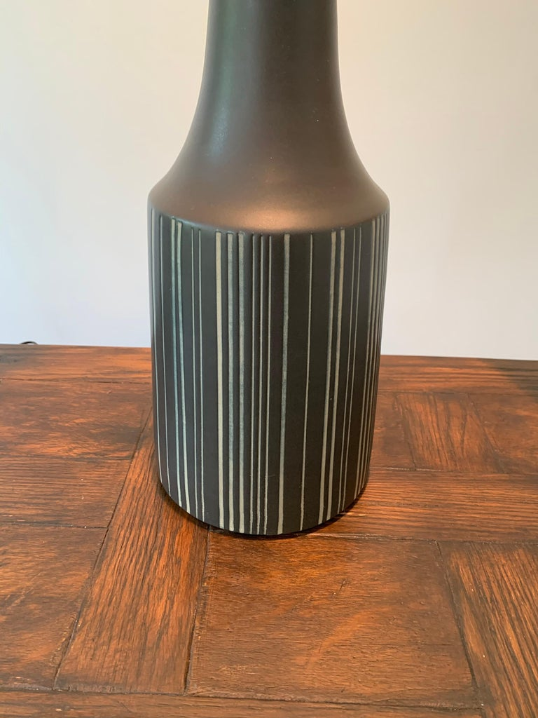 """Pair of black sgraffito table lamps with walnut necks and finials. Slipcast, dipped in glaze, then hand painted with vertical lines. Signed and still have original labels. Measures: Height to top of shade 36.5""""."""