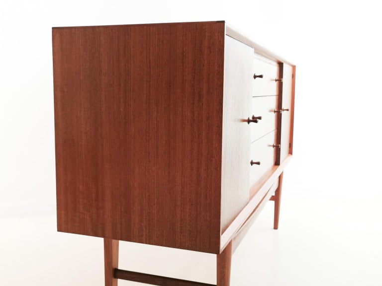 About this item Classic Gordon Russell 1960s sideboard offered in superb condition, having had very little use.  Made in a rich, grained Indian laurel, the sideboard is stamped by the maker and has trumpet-shaped door and drawer pulls. The