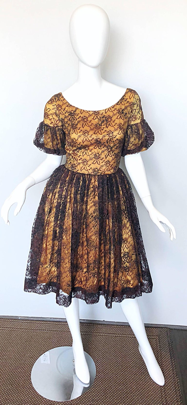 Gorgeous 1950s black and gold silk lace fit n' flare cocktail dress! Features luxurious black French lace with a golden satin underlay, with sparkles of colorful glitter sporadically thorughout. Pretty flounced sleeves. Fitted bodice with a