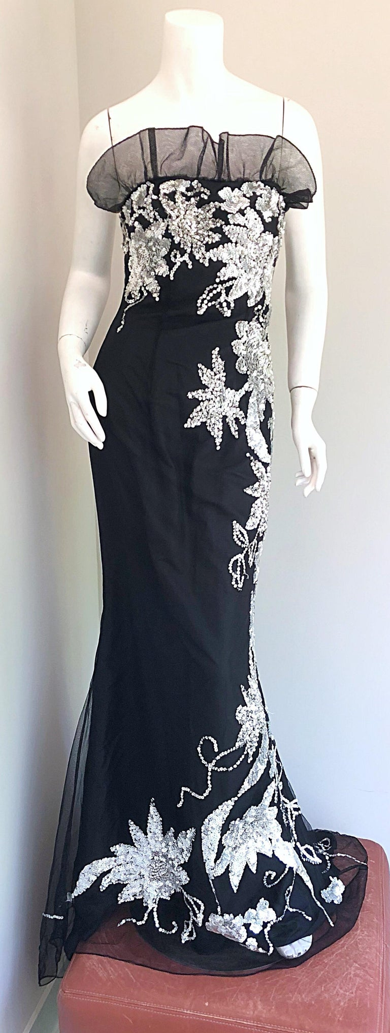 Gorgeous early 1990s black and silver tulle and sequined full length strapless evening dress! Features black taffeta with a tulle overlay. Thousands of hand-sewn silver sequins throughout. Ruffled neckline above the bust. Dramatic train in the back