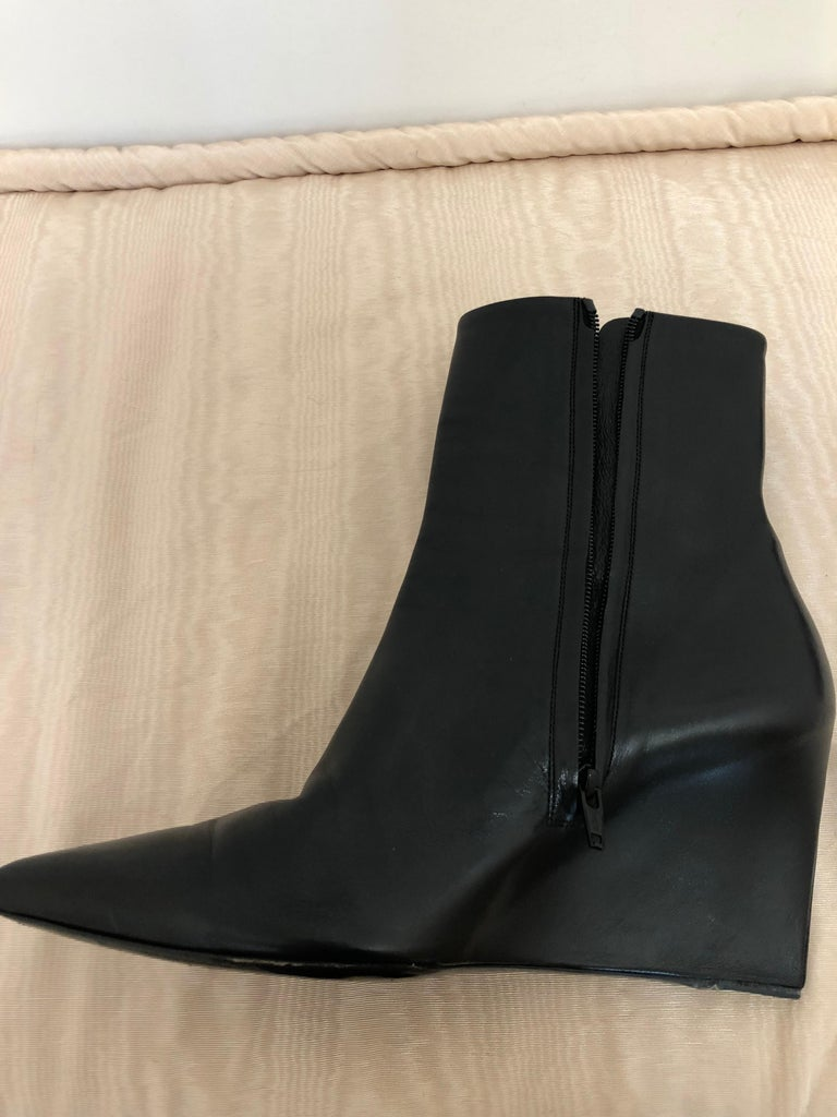 These are wonderful Balenciaga black leather wedges are beautifully crafted of a single layer which encases both the upper and heel. This is a gorgeous and very sleek pair of booties with a pointed top and side zip closure.  We believe they are from