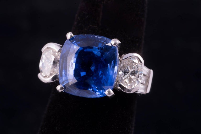 Sapphire and diamond ring. The center sapphire is is cushion cut, weighs approx. 8.75cts, has strong medium blue color and clean clarity. There are 2 oval diamonds on either side that weigh approx. 1.25cts total. There are 6 taper baguette diamonds