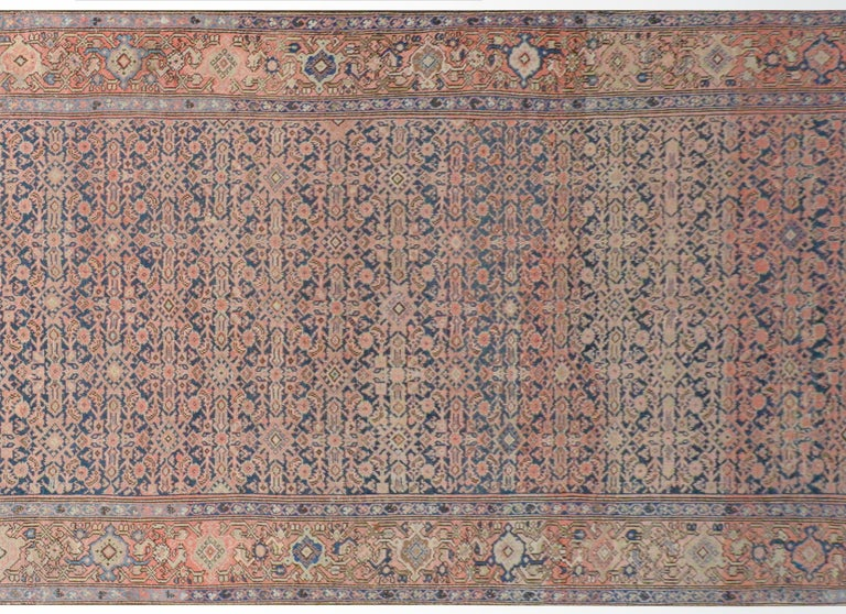 A gorgeous early 20th century Persian Herati rug with a wonderful all-over trellis floral pattern woven in pink, light indigo, and gold, on a dark indigo background surrounded by a wide border with a large-scale floral and scrolling vine pattern.