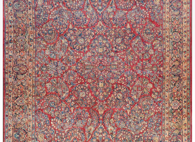 A gorgeous early 20th century Sarouk rug with a fantastic pattern of clusters of myriad flowers all woven in light and dark indigo, cream, orange, and light green vegetable dyed wool on a dark cranberry background. The border is beautiful with